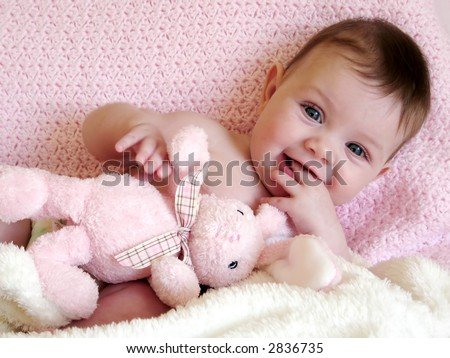 baby girl smiling with bunny rabbit - stock photo