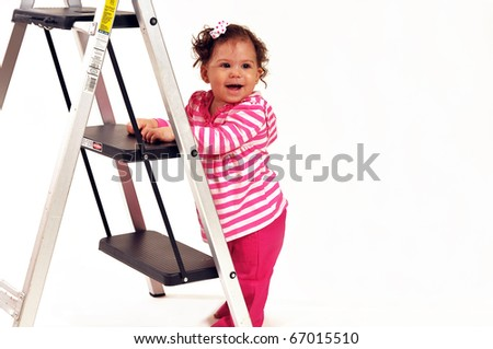 Baby girl, standing against a ladder, smiling and happy over her accomplishment. - stock photo