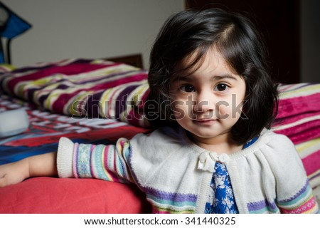 Baby girl standing with bed. - stock photo
