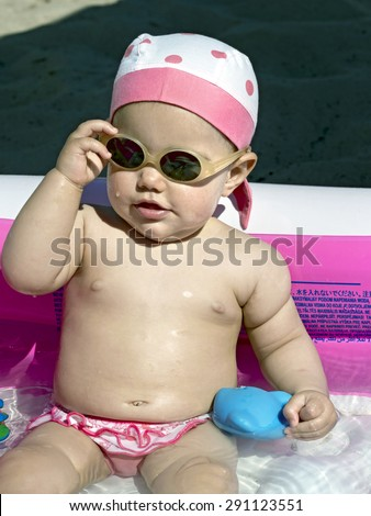baby girl takes off his sunglasses inside an inflatable pool on the beach - stock photo