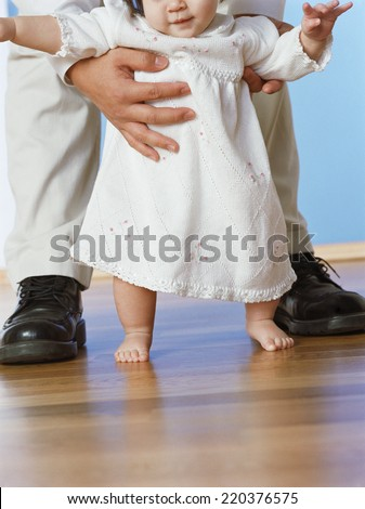 Baby girl taking first steps with fathers help - stock photo
