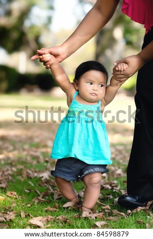 Baby girl taking her first steps with her mom helping her - stock photo