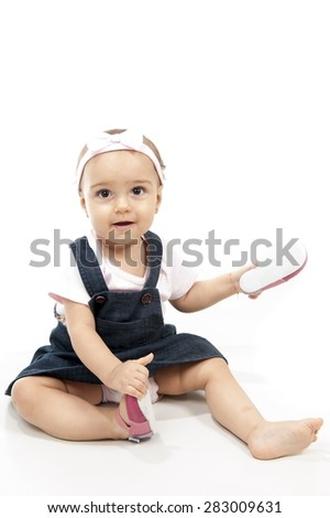 Baby Girl taking off her shoes - stock photo