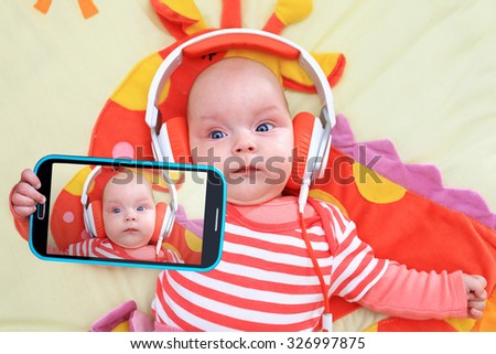 Baby girl taking selfie with a cell phone camera - stock photo