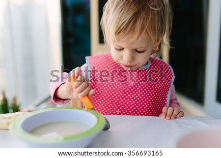 baby girl toddler eating her breakfast porridge on the balcony wearing a pink bib. - stock photo