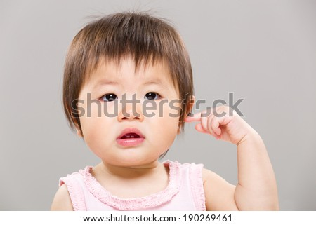 Baby girl touch her ear - stock photo