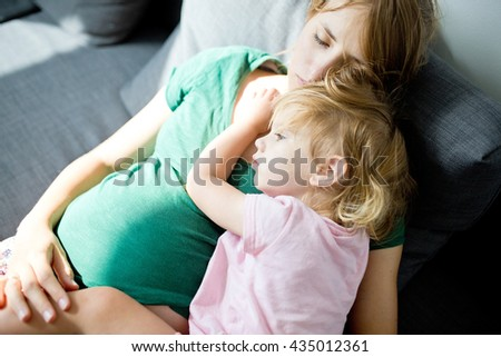 Baby girl two years old sleeping on a pregnant mothers stomach. Mother and daughter together - stock photo
