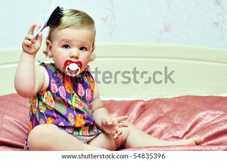 baby girl using comb at home on the bed