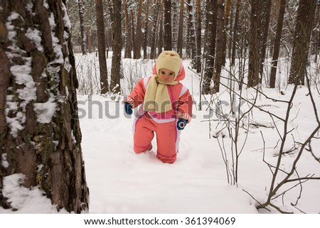 Baby girl walking in the winter forest - stock photo