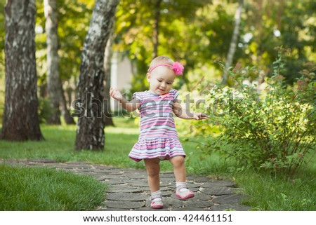 Baby girl walking outdoors dressed in pink stripped dress. Happy kid. Happy childhood.