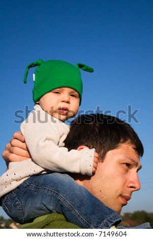 Baby girl walking with her daddy on a sunny evening in May - stock photo