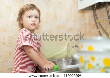 Baby girl washing dishes in kitchen
