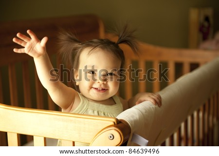 Baby girl waving hand and standing up in crib