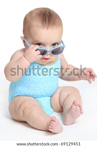 Baby girl wearing a blue swimsuit and sunglasses - stock photo