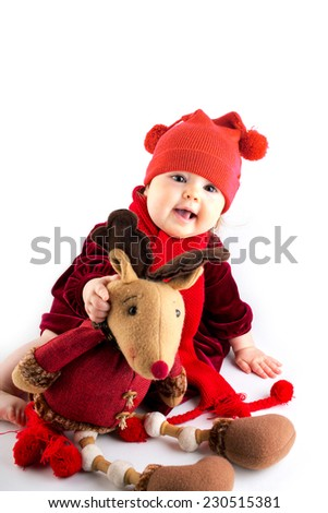 Baby girl wearing christmas hat with reindeer toy  - stock photo