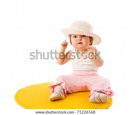 Baby girl wearing panama sitting on carpet isolated - stock photo