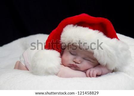 Baby girl wearing red santa hat while sleeping and peeking at times - stock photo
