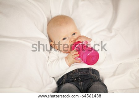 baby girl with a baby bottle lying on a blanket - stock photo