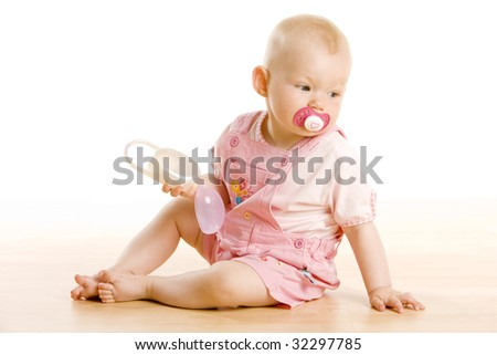 baby girl with a baby pacifier sitting on the floor