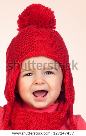 Baby girl with a funny wool red hat isolated on orange background - stock photo