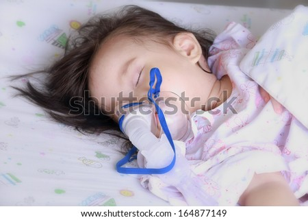 baby girl with a mask for inhaler in hospital. - stock photo
