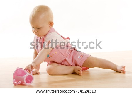 baby girl with a mug sitting on the floor
