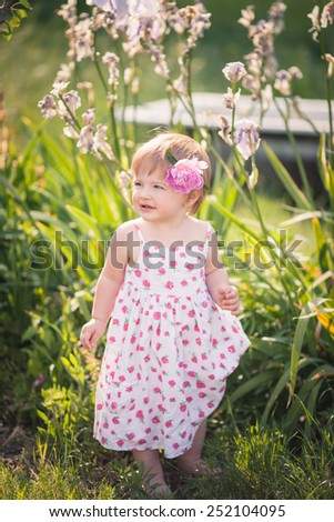 baby girl with blue eyes blond hair and pink peony in her hair in summer garden with bright flowers.  She dressed on white with floral pattern summer dress.  full length portrait - stock photo