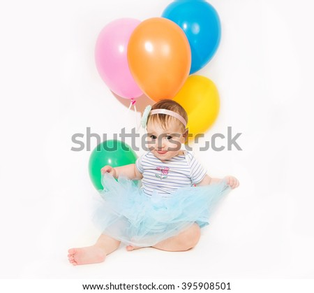 Baby girl with bunch of colorful balloons in his hand - stock photo
