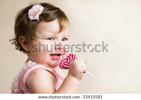 Baby girl with chubby cheeks eating a sticky lollipop - stock photo