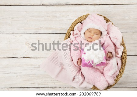 Baby girl with gift sleeping in basket on wooden background, newborn holding present. Birthday party invitation card - stock photo
