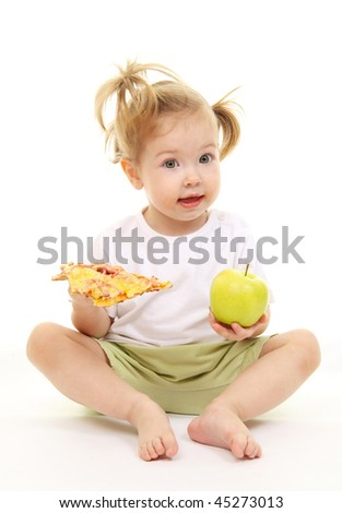 Baby girl with green apples and pizza - stock photo
