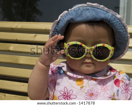 baby girl with hat and sunglasses - stock photo