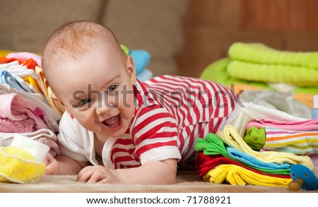 baby girl with heap of children's wear - stock photo