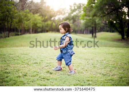 Baby girl with jean dress walking on the grass field in the park