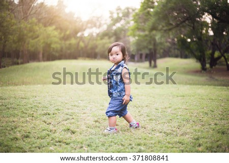Baby girl with jean dress walking on the grass field in the park - stock photo