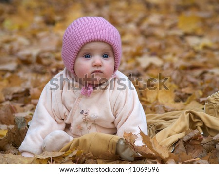Baby girl with lost expression in autumn park - stock photo
