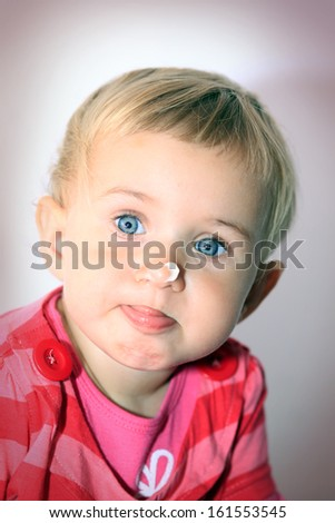 Baby girl with lotion on her face - stock photo