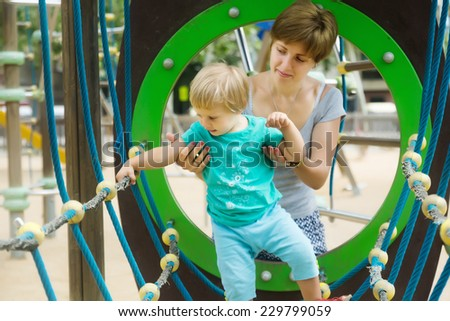Baby girl with mother developing dexterity at playground  - stock photo