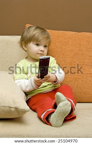 baby girl with remote control on  sofa - stock photo