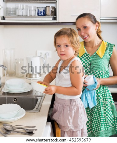 Baby girl with smiling woman washing plates in kitchen