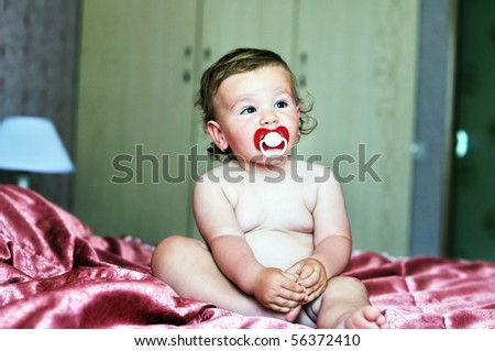 baby girl  with soother sitting on the bed