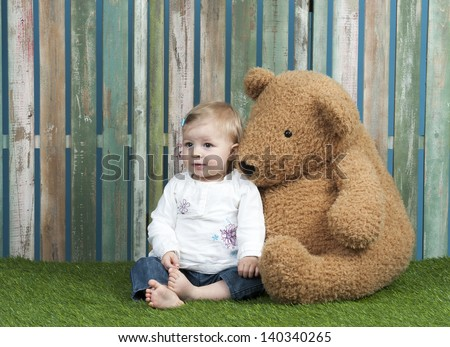 baby girl with teddy bear, seated in font of a fence