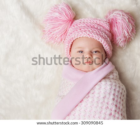 Baby Girl Wrapped Up in Newborn Blanket, New Born Kid Bundled Hat, One Month on Carpet - stock photo
