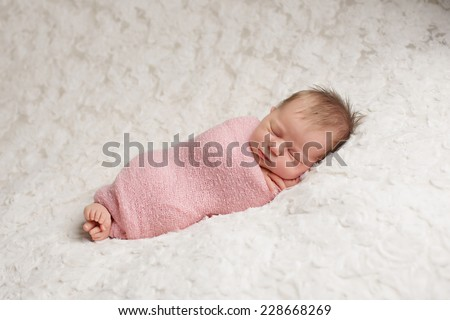 Baby girl wrapped up in pink blanket - stock photo