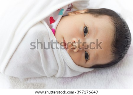 Baby girl wrapping infants in cloths in order to prevent limb movement. - stock photo