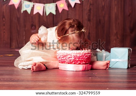 Baby girl 1 year old celebrating first birthday in room. Eating cake. Birthday decoration. Childhood. - stock photo