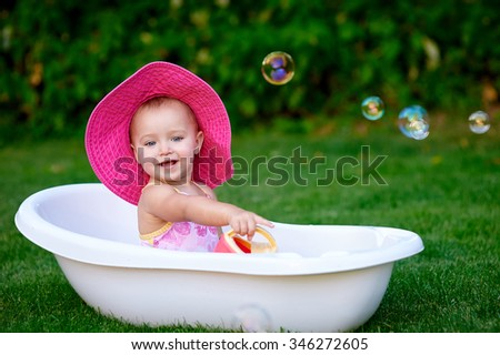 Baby girl 1-2 year old taking bath with soap foam outdoors. Childhood. Washing - stock photo