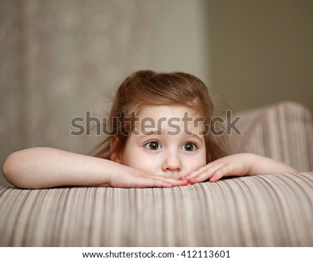 Baby girl 4-5 years. With a frightened look. Hid, peeking out. - stock photo