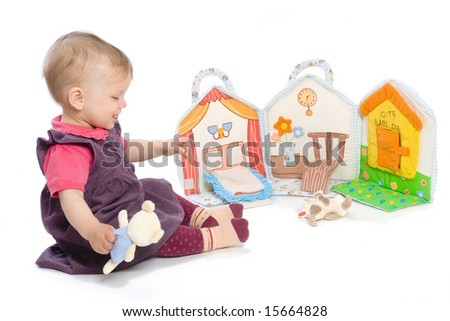 Baby girls sitting on floor playing with stuffed story book. Isolated on white. Toys are officially property released. - stock photo