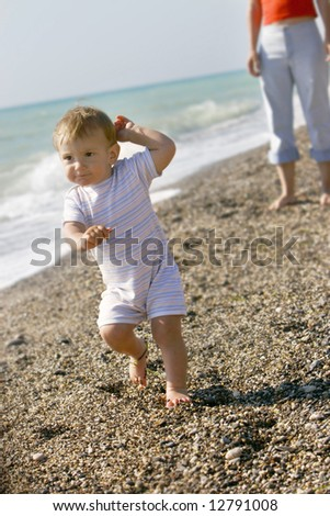 baby going away from mother on beach - stock photo